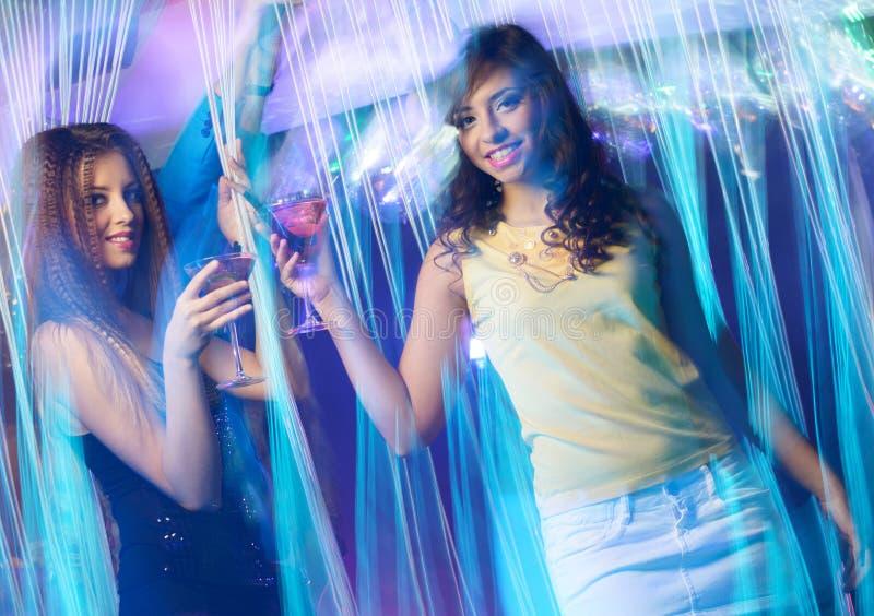 Lyckliga unga flickor på nattklubben royaltyfri fotografi
