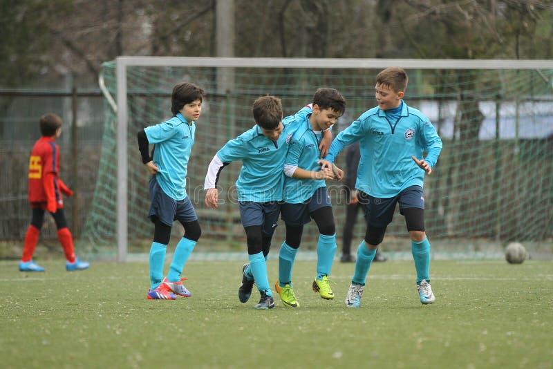 Lyckliga unga fotbollsspelare efter ett mål fotografering för bildbyråer