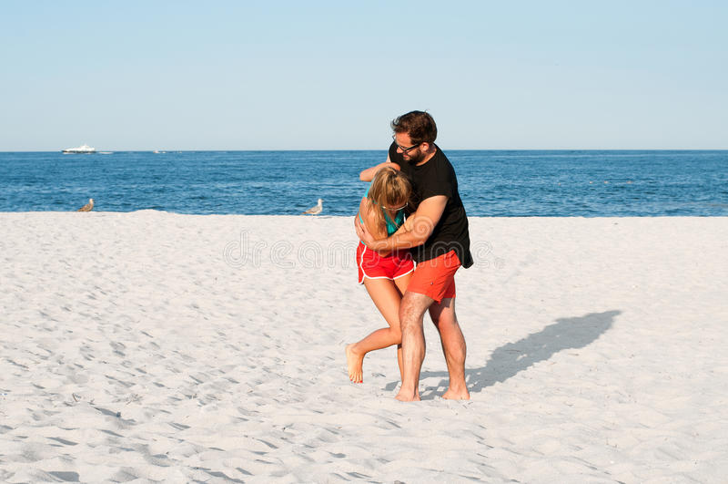 Lyckliga unga glade par under sommarferier semestrar tillsammans på den tropiska stranden royaltyfri bild