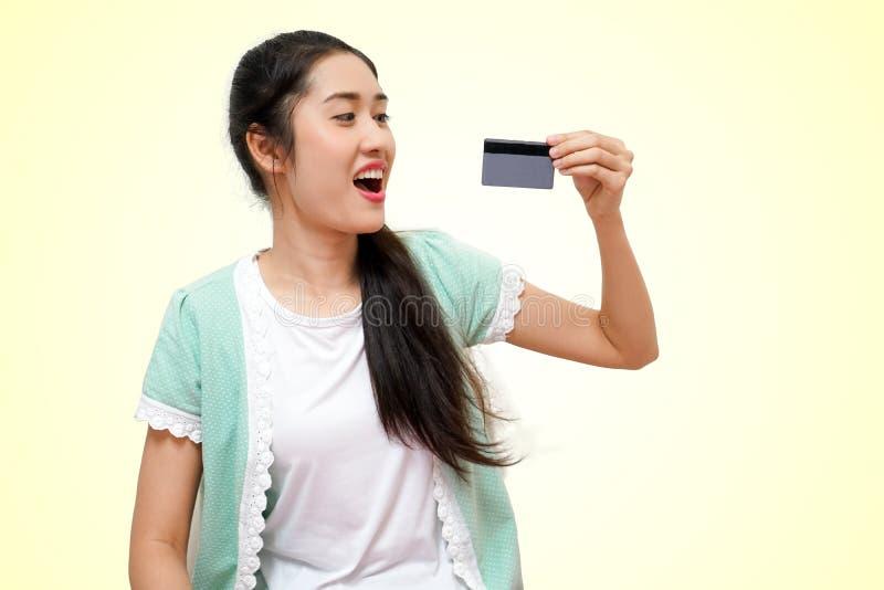 Lyckliga unga härliga kvinnor i skjorta och vänster överraskning för anseende för handhållkort som isoleras på gul mjuk ba royaltyfria bilder