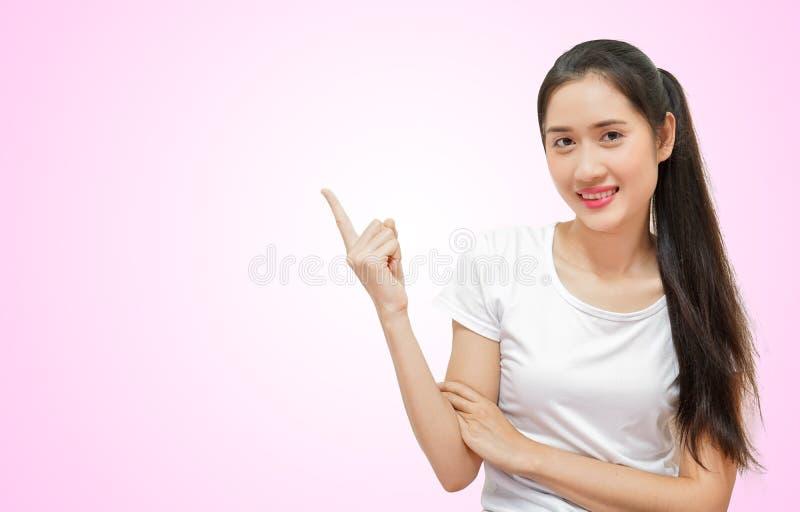 Lyckliga unga härliga kvinnor i t-sirtassistenten pekade anseende som isolerades på rosa mjuk bakgrund royaltyfri bild