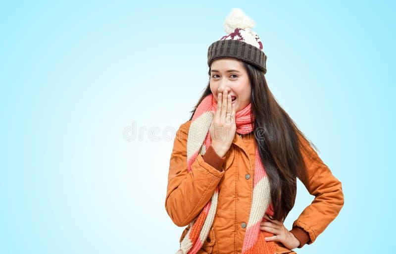 Lyckliga unga härliga kvinnor i vinterkläder som förvånas som isoleras på blå bakgrund royaltyfri foto