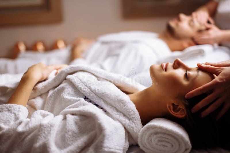 Lyckliga unga härliga par som tycker om den head massagen på brunnsorten arkivfoto