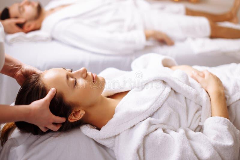 Lyckliga unga härliga par som tycker om den head massagen på brunnsorten arkivbild