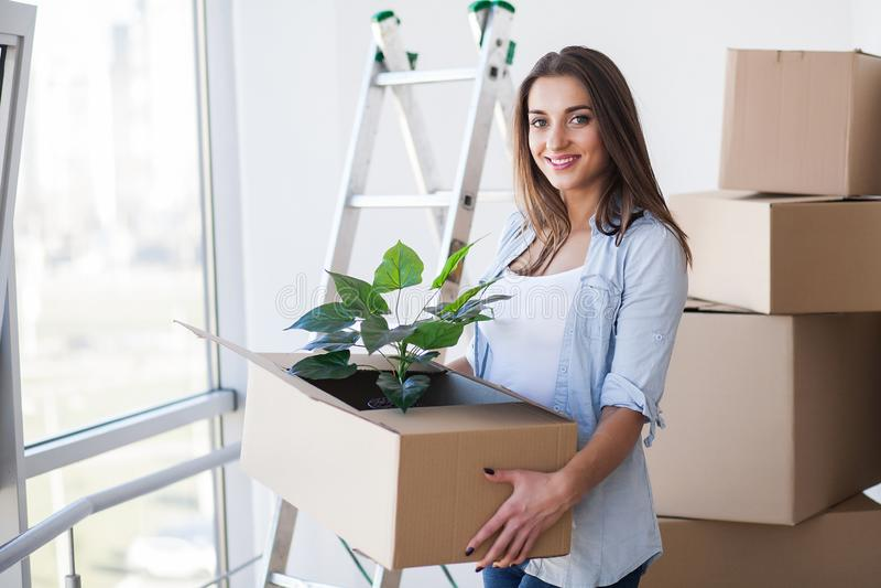 Lyckliga unga h?llande flyttningaskar f?r vuxen kvinna i tomt rum i ett nytt hus arkivfoto