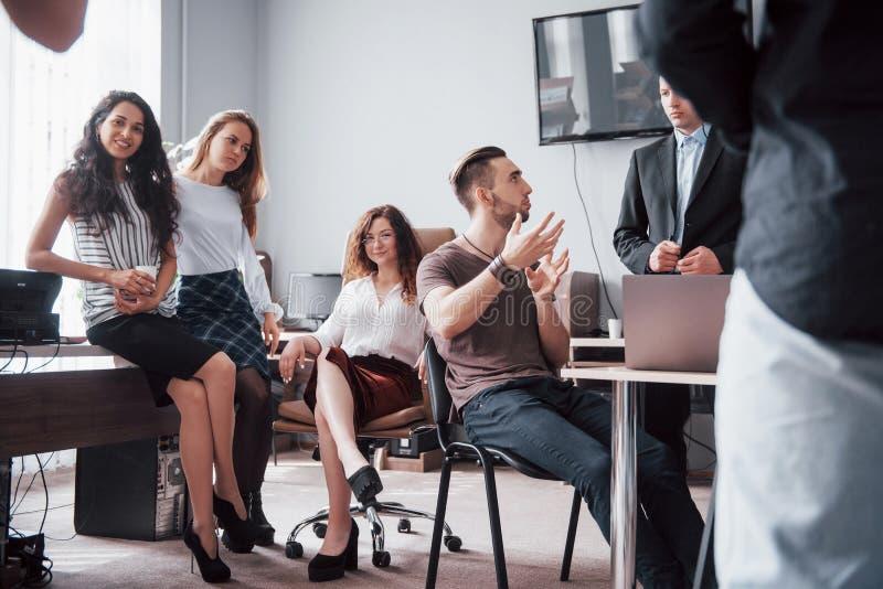 Lyckliga unga kollegor som diskuterar i möte på det idérika kontoret royaltyfri foto