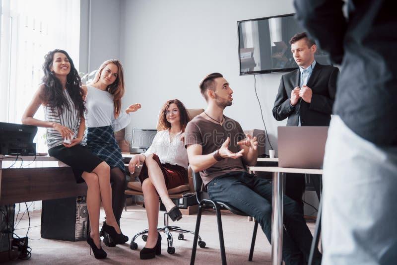 Lyckliga unga kollegor som diskuterar i möte på det idérika kontoret royaltyfri bild
