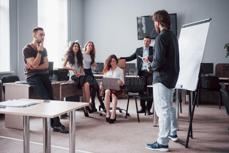 Lyckliga unga kollegor som diskuterar i möte på det idérika kontoret arkivbild