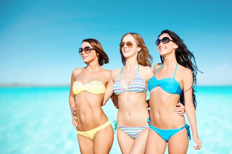 Lyckliga unga kvinnor i bikinier över blå himmel och havet royaltyfri bild