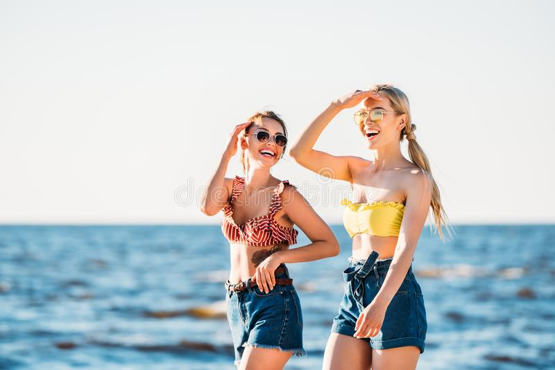 lyckliga unga kvinnor i solglasögon som tillsammans går arkivfoto