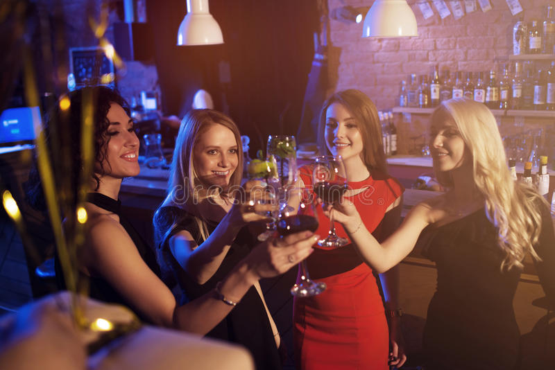 Lyckliga unga kvinnor med exponeringsglas av vin och coctailar som tycker om en natt ut i stilfull stång arkivbilder