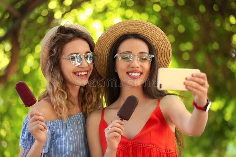 Lyckliga unga kvinnor med läckra glassar som tar selfie royaltyfri fotografi