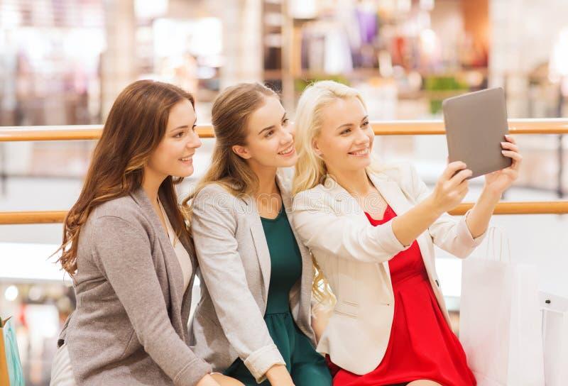 Lyckliga unga kvinnor med minnestavlaPC och shoppingpåsar arkivbilder