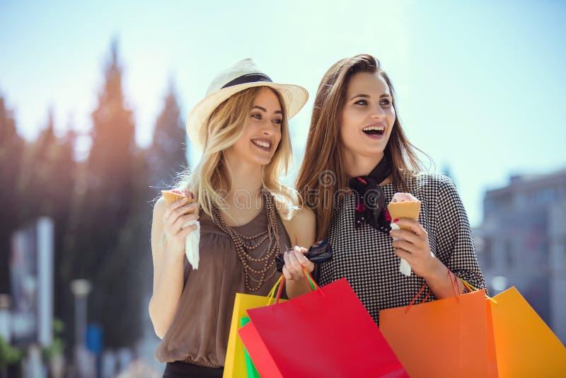 Lyckliga unga kvinnor med shoppingpåsar och glass som har gyckel arkivfoto