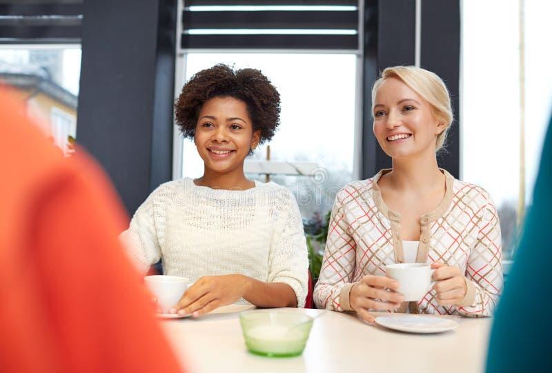 Lyckliga unga kvinnor som dricker te eller kaffe på kafét royaltyfria bilder