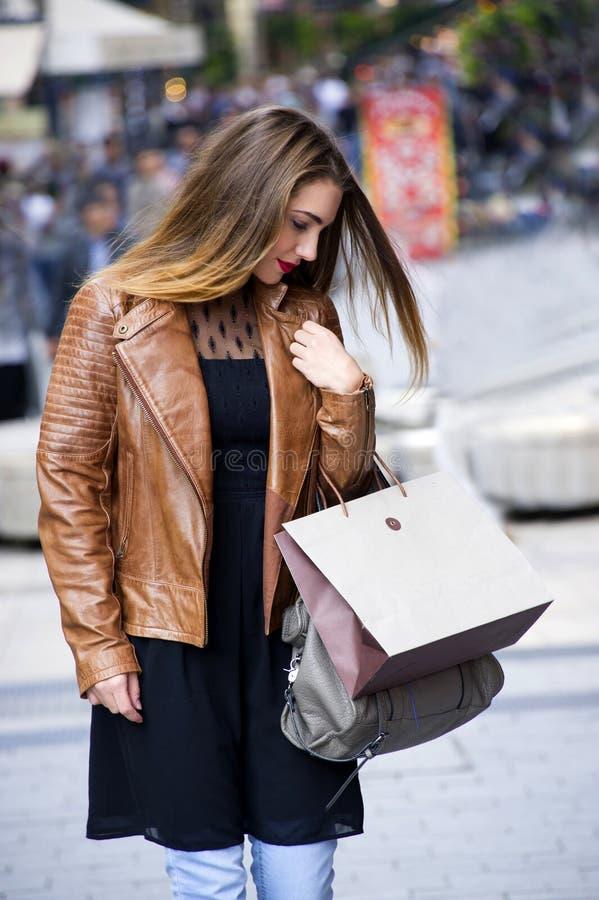 Lyckliga unga kvinnor som går och shoppar i stad Moderiktig kvinnakonsument som ser shoppafönstren arkivfoton
