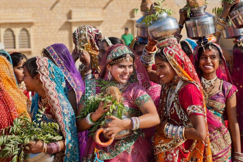 Lyckliga unga kvinnor som går på den berömda ökenfestivalen royaltyfri bild