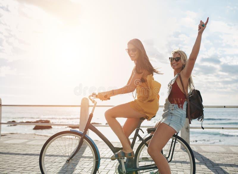 Lyckliga unga kvinnor som tycker om cykelritt arkivfoton