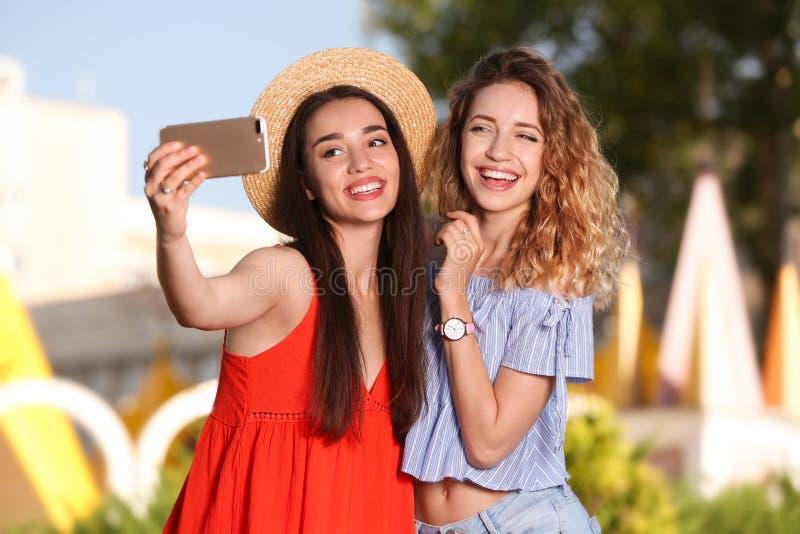 Lyckliga unga kvinnor som utomhus tar selfie fotografering för bildbyråer