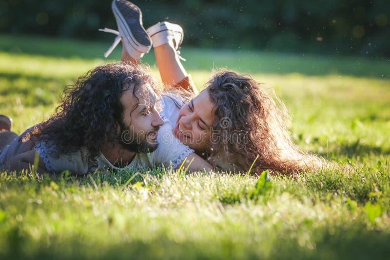 Lyckliga unga lockiga par som ligger på det gröna gräset i den soliga sommaren, parkerar arkivfoto