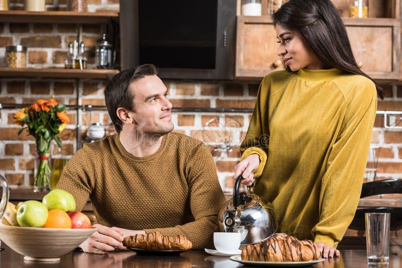 lyckliga unga multietniska par som ler sig, medan ha frukosten royaltyfria bilder