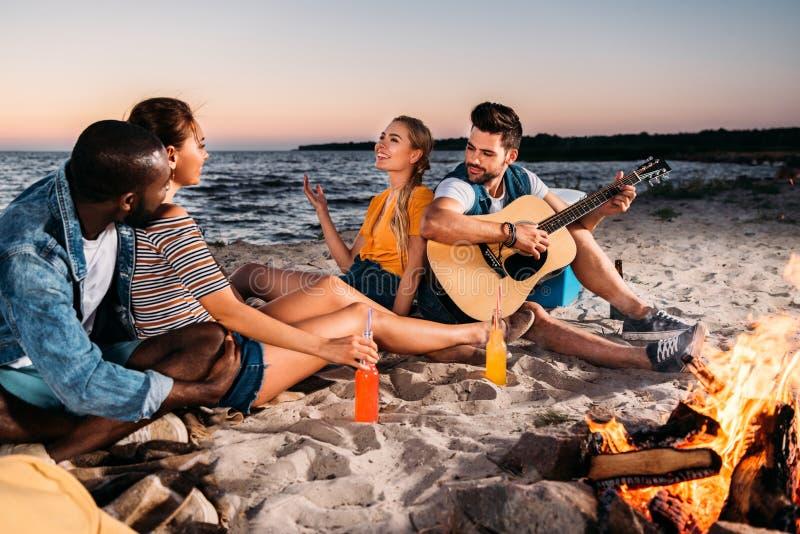lyckliga unga multietniska vänner som tycker om gitarren och tillsammans spenderar tid på den sandiga stranden royaltyfri bild