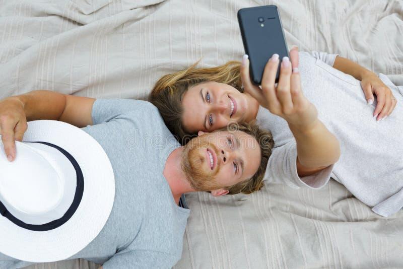 Lyckliga unga par för stående som tar selfie royaltyfri bild