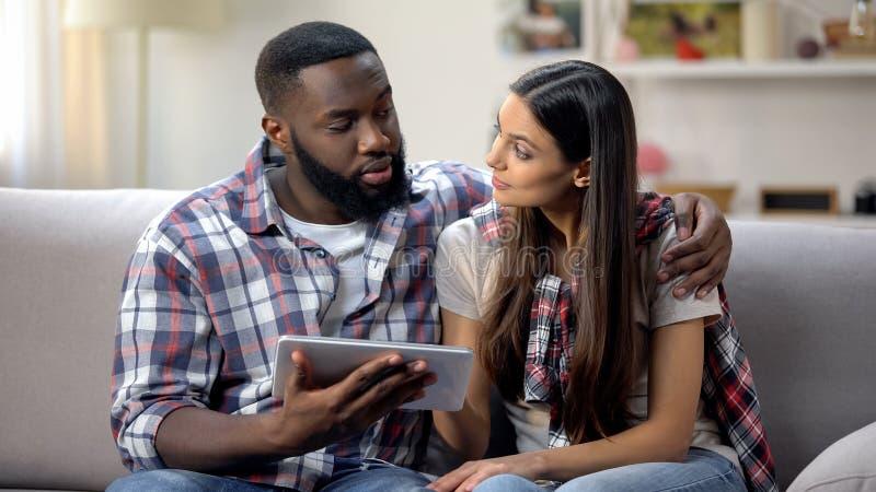 Lyckliga unga par genom att använda den digitala minnestavlan hemma och att boka hotellet direktanslutet, semester arkivbilder