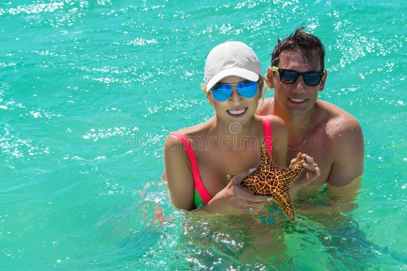Lyckliga unga par i det karibiska havet, rymmer de en levande sjöstjärna royaltyfria bilder