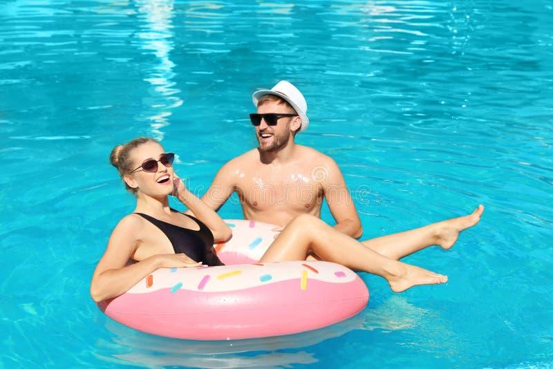 Lyckliga unga par med den uppblåsbara cirkeln royaltyfri fotografi