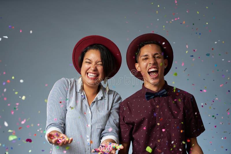 Lyckliga unga par med konfettier arkivfoton