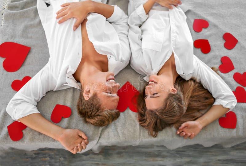 Lyckliga unga par med röda hjärtor som hemma ligger på säng royaltyfria foton