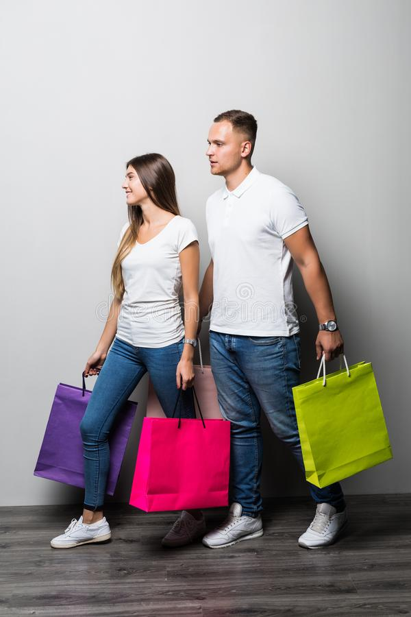 Lyckliga unga par med shoppingpåsar som omfamnar och ser bort på vit bakgrund royaltyfria foton