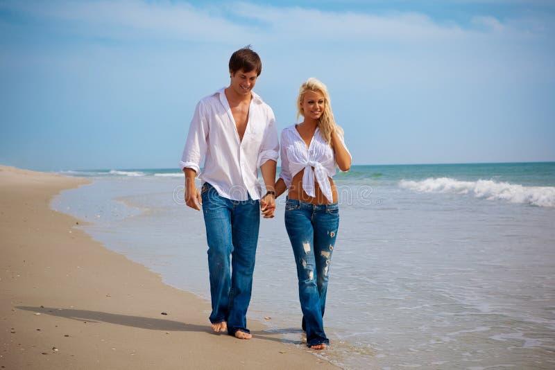 Lyckliga unga par på stranden royaltyfri bild