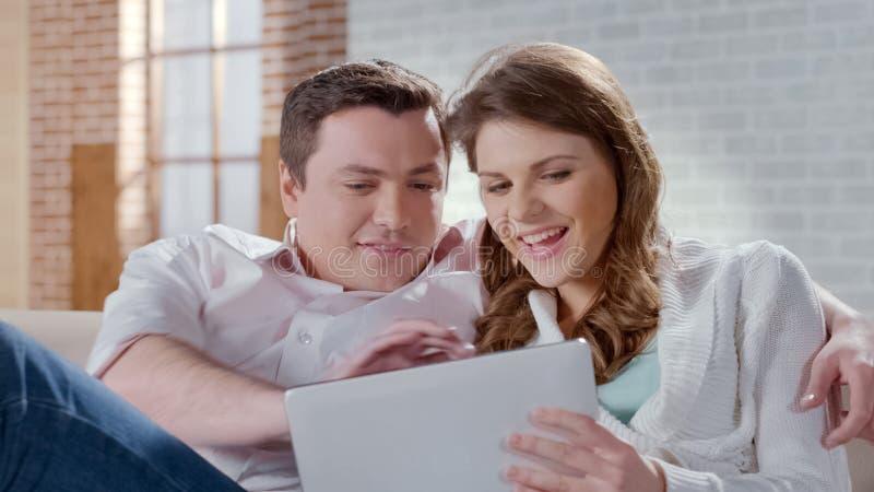 Lyckliga unga par som beskådar foto på minnestavlan som väljer objekt i online-, shoppar royaltyfri bild