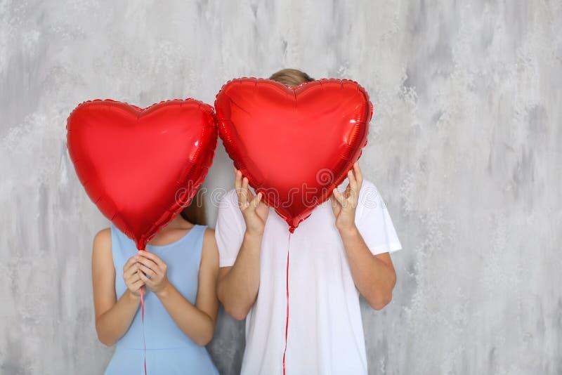 Lyckliga unga par som döljer framsidor bak hjärta, formade röda ballonger nära den gråa väggen royaltyfria foton