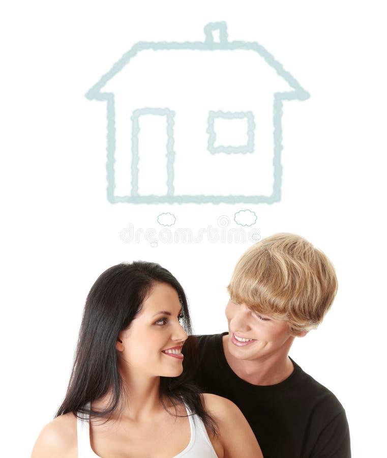 Lyckliga unga par som drömm om deras nya utgångspunkt arkivbild