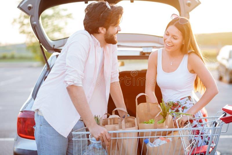 Lyckliga unga par som går tillbaka från livsmedelsbutikshopping som laddar pappers- påsar med mat in i en bilstam arkivbilder