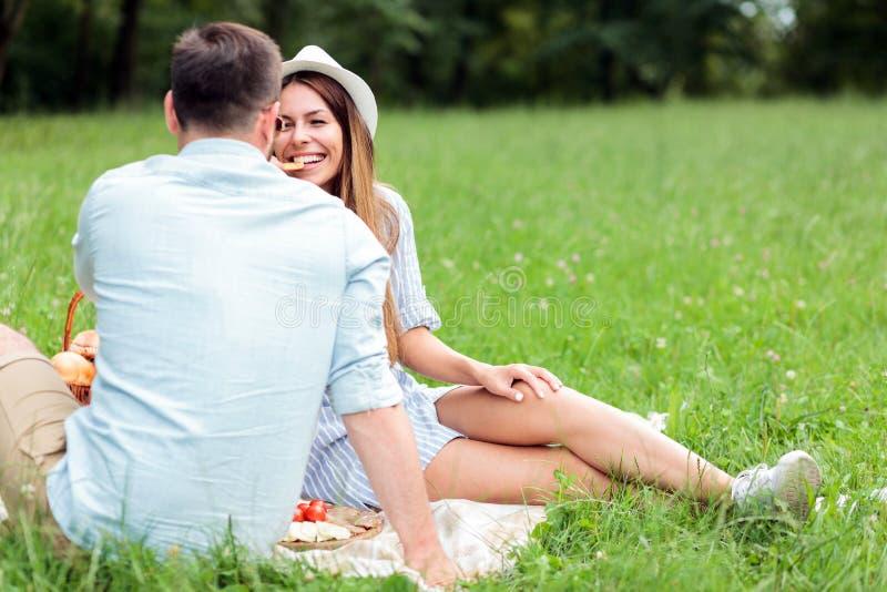 Lyckliga unga par som har en stor tid i, parkerar och att sitta på en picknickfilt royaltyfria bilder