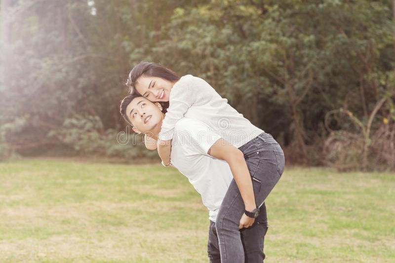 Lyckliga unga par som ler och, har gyckel på staden parkerar arkivbild