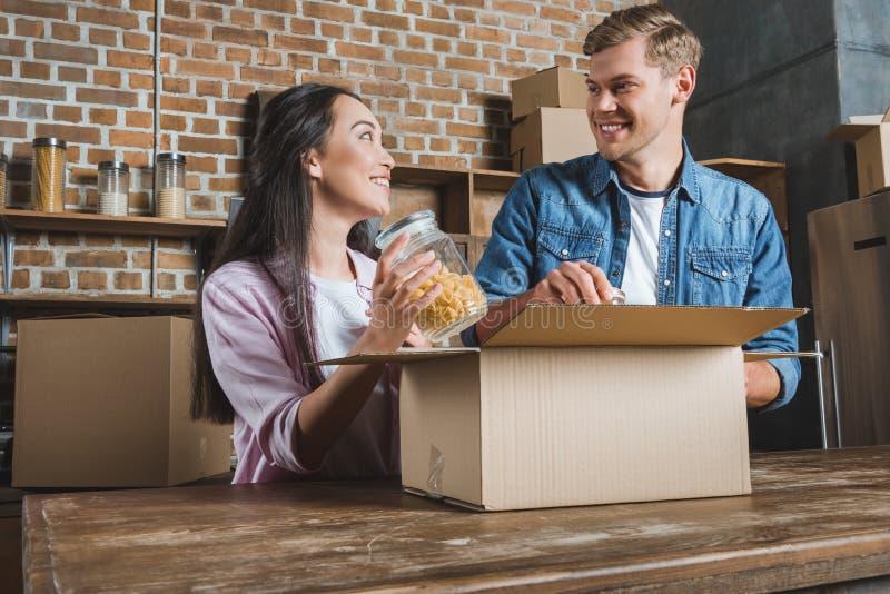 lyckliga unga par som packar upp askar på kök, medan flytta sig in i fotografering för bildbyråer
