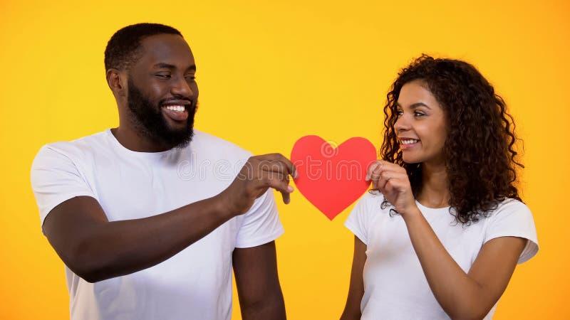 Lyckliga unga par som rymmer röd pappers- hjärta och ler som är riktig förälskelse och omsorg royaltyfri foto