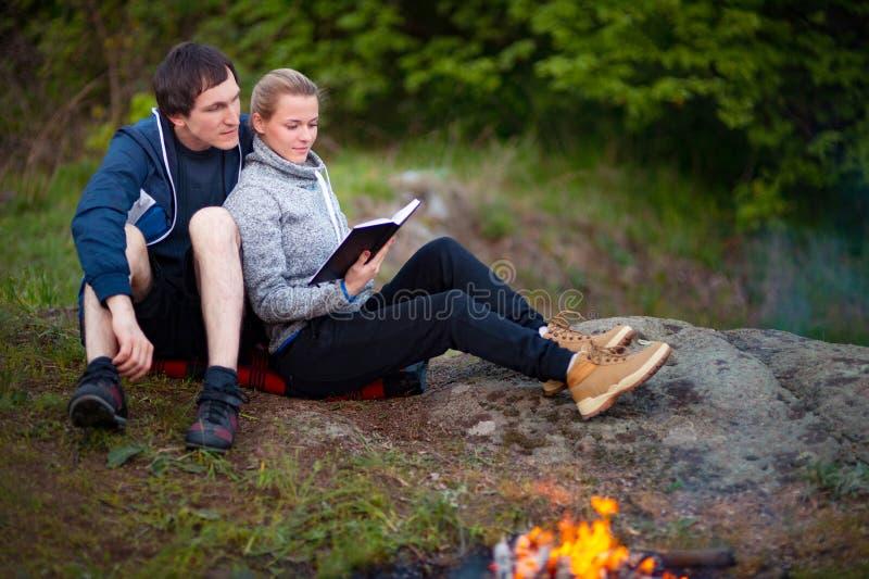 Lyckliga unga par som sitter nära lägereld och läseboken arkivfoto