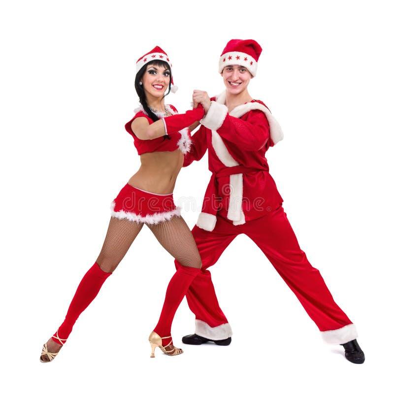 Lyckliga unga par som slitage Santa Claus kläder arkivbilder