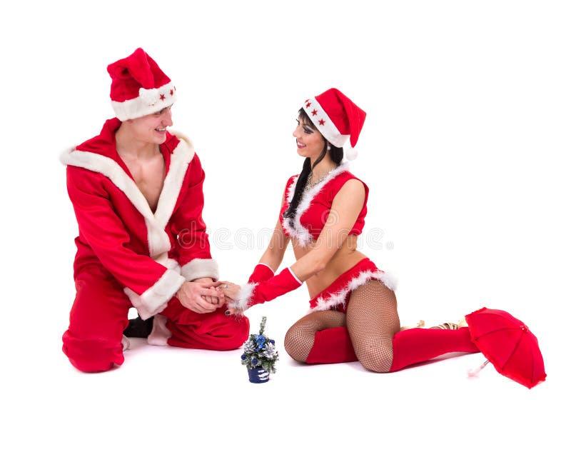 Lyckliga unga par som slitage Santa Claus kläder arkivfoto