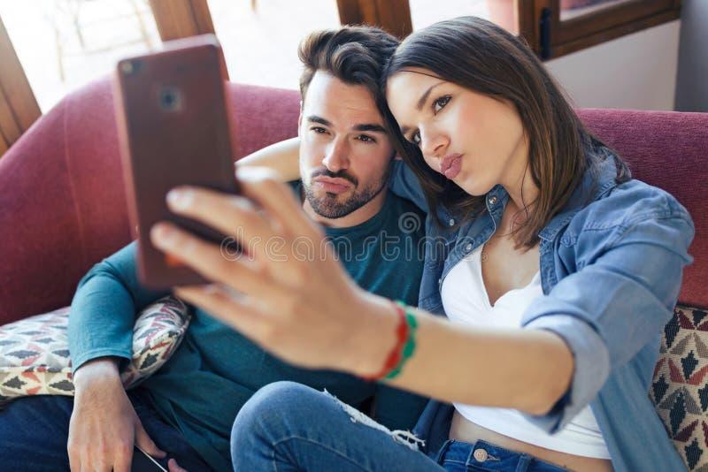 Lyckliga unga par som tar en selfie med den smarta telefonen, medan sitta på soffan hemma fotografering för bildbyråer