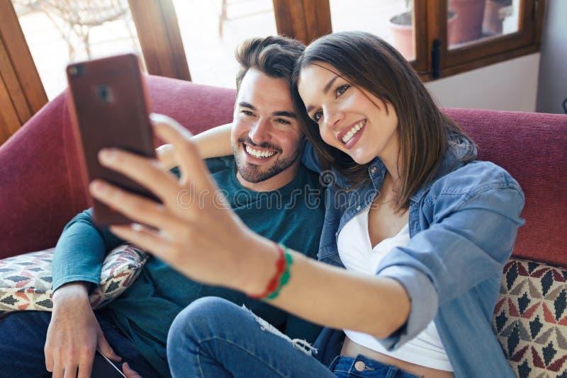 Lyckliga unga par som tar en selfie med den smarta telefonen, medan sitta p? soffan hemma royaltyfri foto