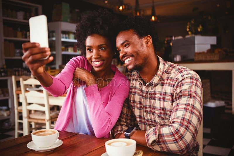 Lyckliga unga par som tar selfie i kafeteria arkivfoto