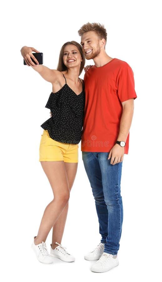 Lyckliga unga par som tar selfie på vit arkivfoton