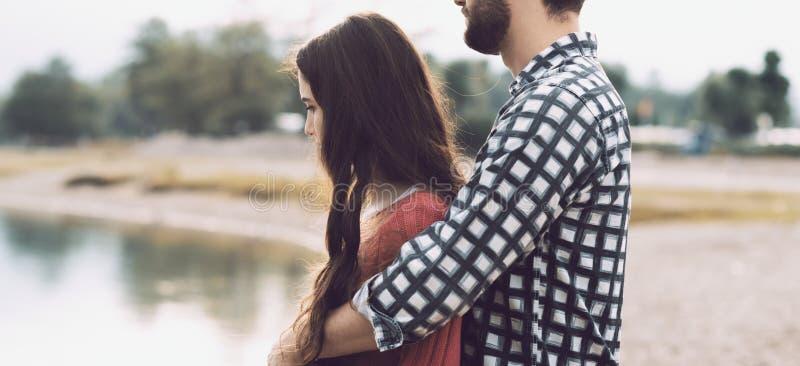Lyckliga unga par som tycker om på stranden royaltyfria foton